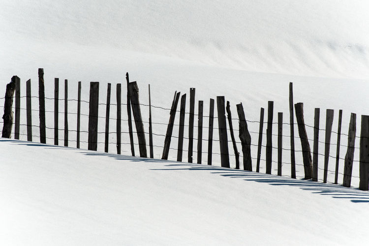 Fence on snow covered land against sky