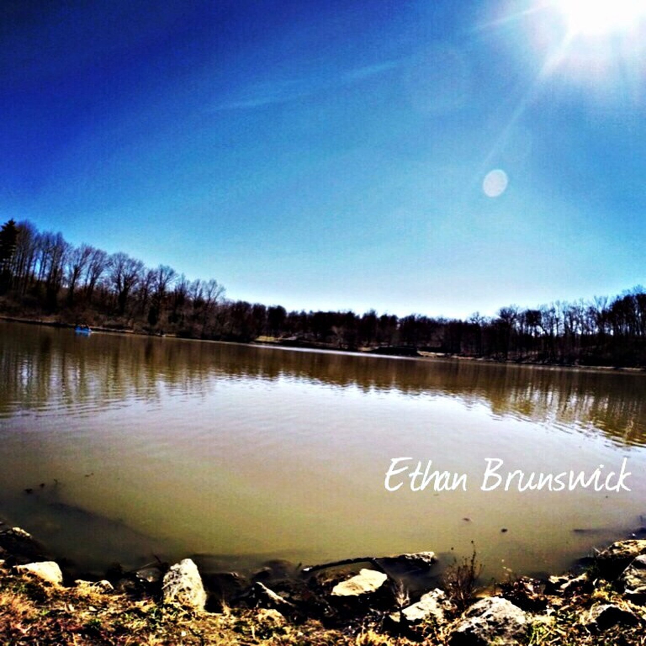 tranquil scene, tranquility, water, lake, scenics, reflection, beauty in nature, nature, clear sky, blue, text, non-urban scene, sunlight, winter, western script, sky, snow, cold temperature, outdoors, idyllic