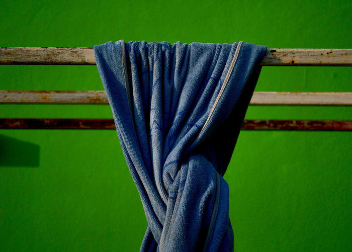 Close-up of blue towel against green wall