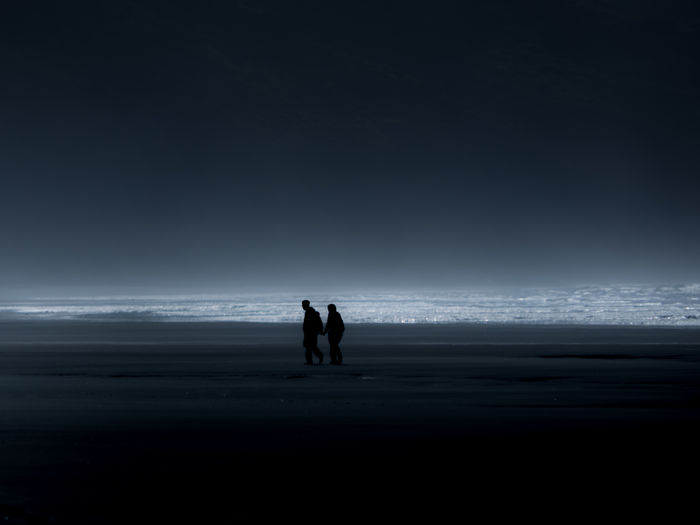 Couple walking on sand at beach against sky