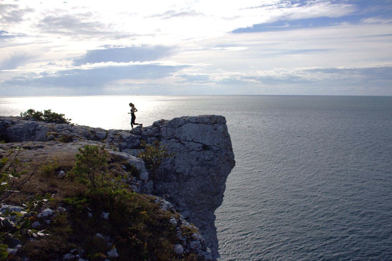 VIEW OF WOMAN RUNNING ON CLIFF