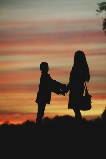 Silhouette of woman standing with her son at sunset
