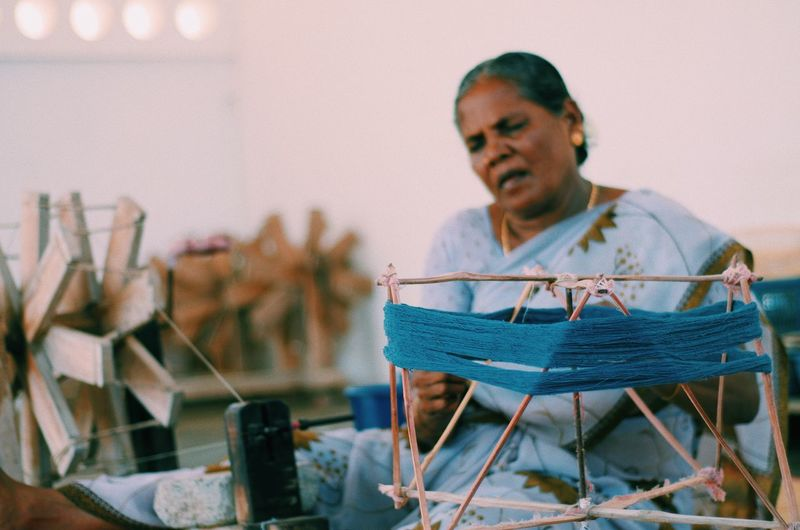 Senior woman weaving loon in workshop