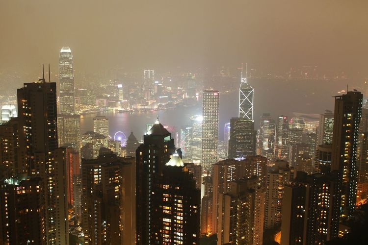 High Angle View Of Illuminated Cityscape At Victoria Harbour