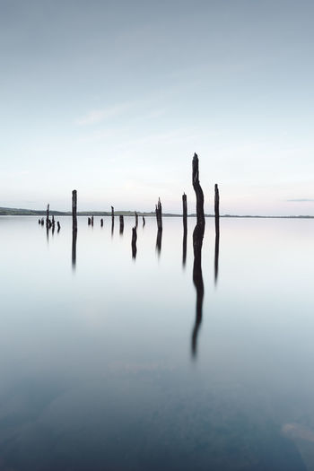 Wooden Posts In Sea Against Sky At Dusk