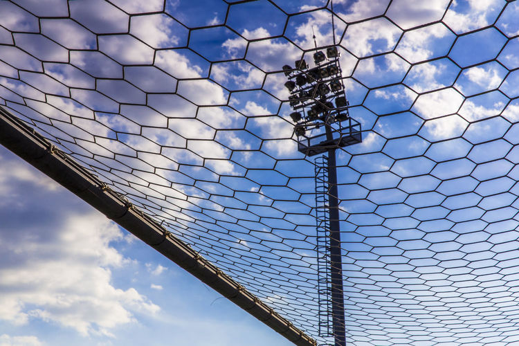 Low Angle View Of Floodlight Against Sky Seen Through Fence