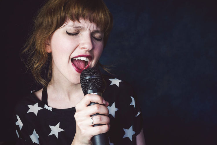 One Person Indoors  Singing Holding Input Device Young Adult Microphone Headshot Front View Portrait Performance Music Studio Shot Singer  Adult Mouth Mouth Open Musician Casual Clothing Black Background Hairstyle Beautiful Woman Singer  Talent Rock Music