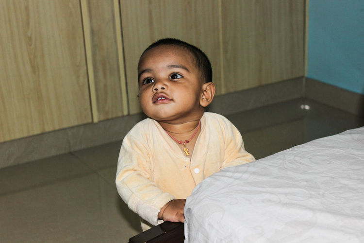 Cute boy sitting by bed at home