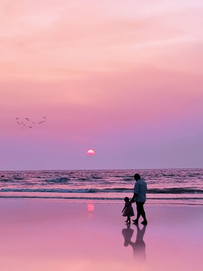 Man on beach against sky during sunset