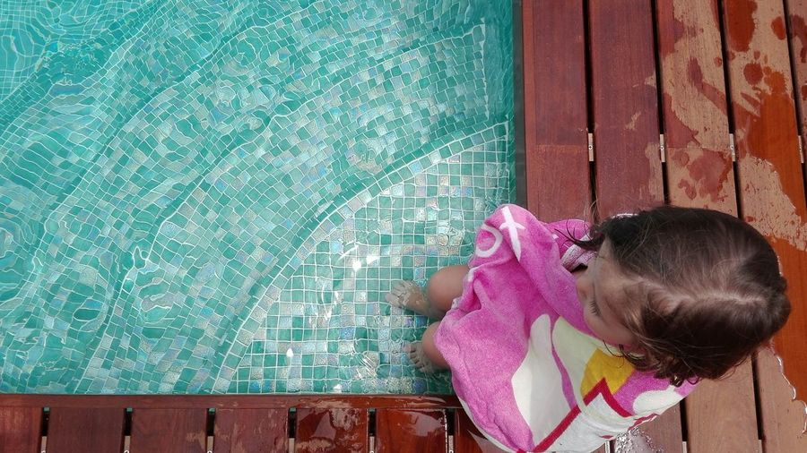 High angle view of girl wrapped in towel sitting at poolside