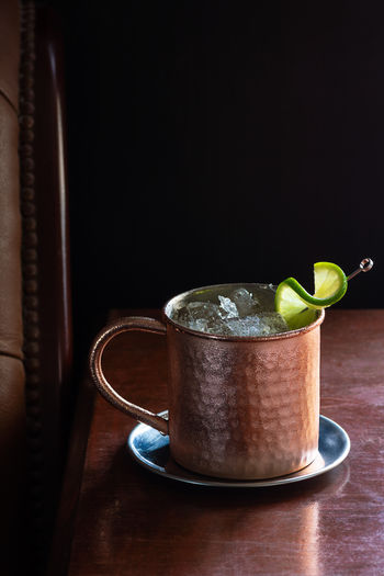Cold Moscow Mule Cocktail in Copper Mug with Crushed Ice and Lime Garnish in Dark Luxurious Bar Table No People Fruit Wood - Material Still Life Brown Citrus Fruit Green Color Moscow Mule Moscow Mule Cup Copper  Copper Mug Mug Cup Copper Cup Drink Drinks Cocktail Cocktails Beverage Ginger Beer Gingerale Ginger Ale Ginger Vodka Lime Citrus  Black Black Background Copy Space Bar Bar - Drink Establishment Luxury Leather Nobody Vertical Alcohol Liquor Alcoholic Drink Mixed Drink Cold Temperature Cold Ice Crushed Ice Metal Mule Moscow