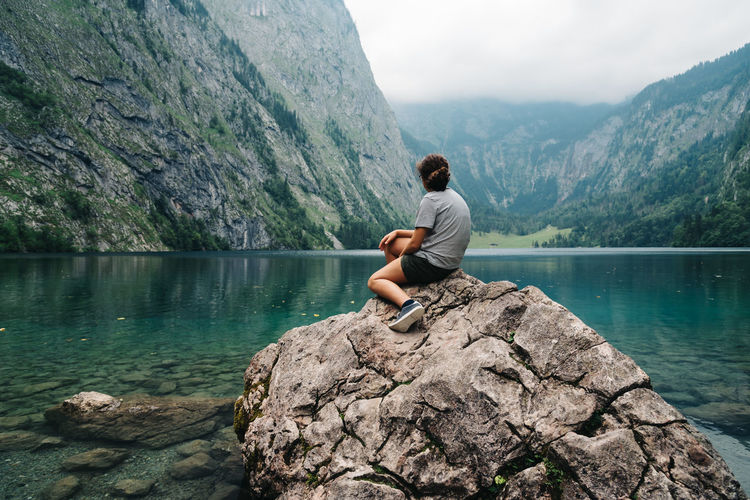 Rear View Of Young Woman Sitting At Lake Against Mountain
