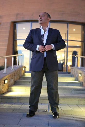 Businessman buttoning blazer while standing against building