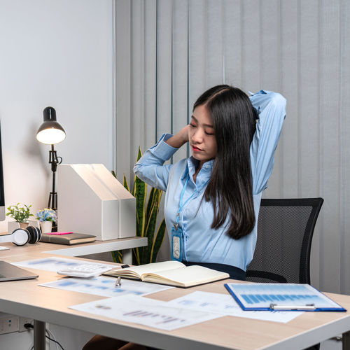 Young businesswoman reading book while sitting at office