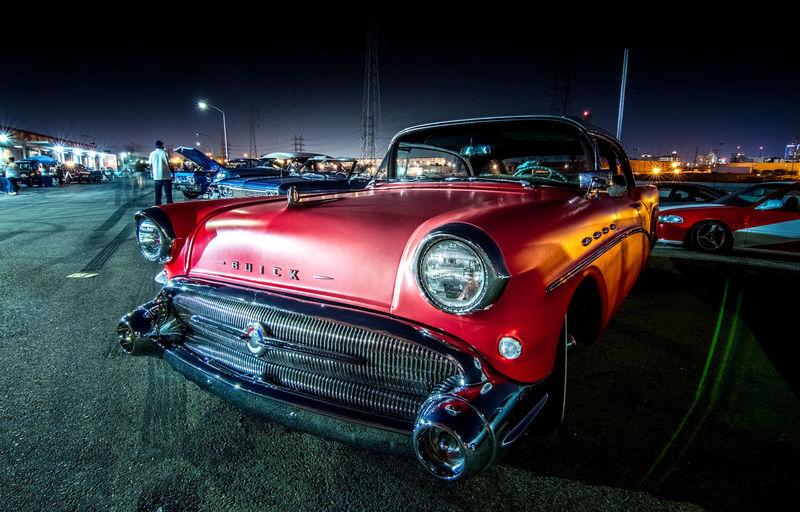 Cars on illuminated car against sky at night