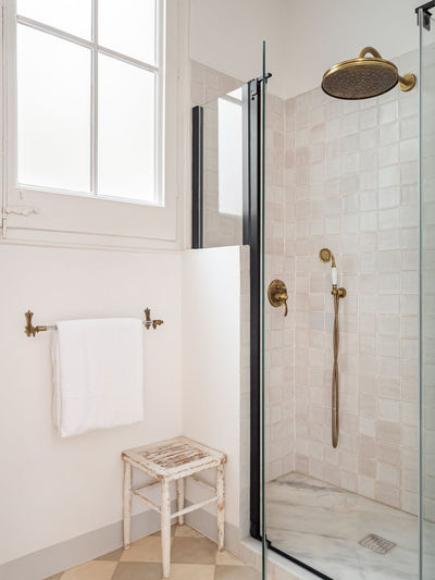 Vintage beige color bathroom with shower zone, window, towel and wooden stool.