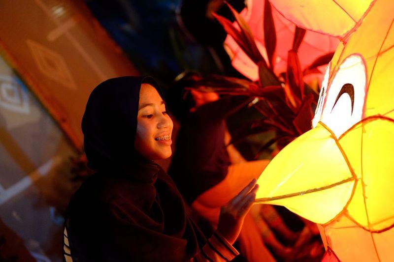 Smiling Teenage Girl Touching Illuminated Lantern