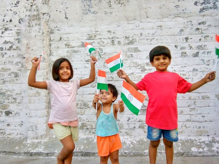 Portrait of happy children with indian flags standing against wall