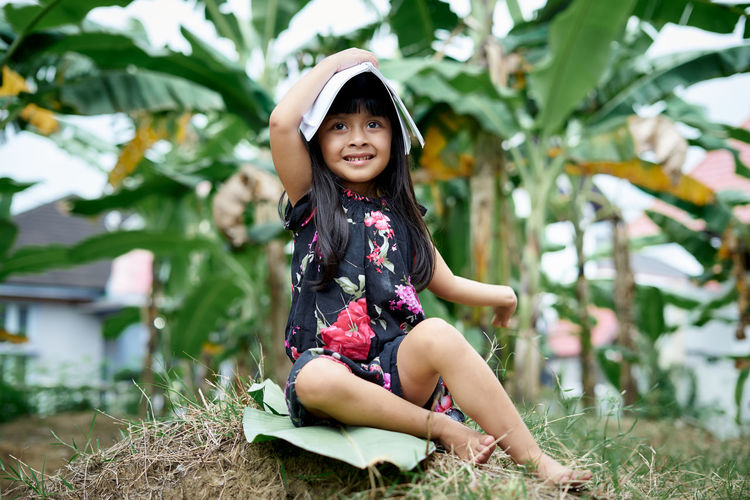 Portrait of a smiling girl sitting on field