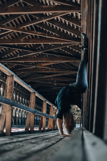 Rear view of woman sitting on railing
