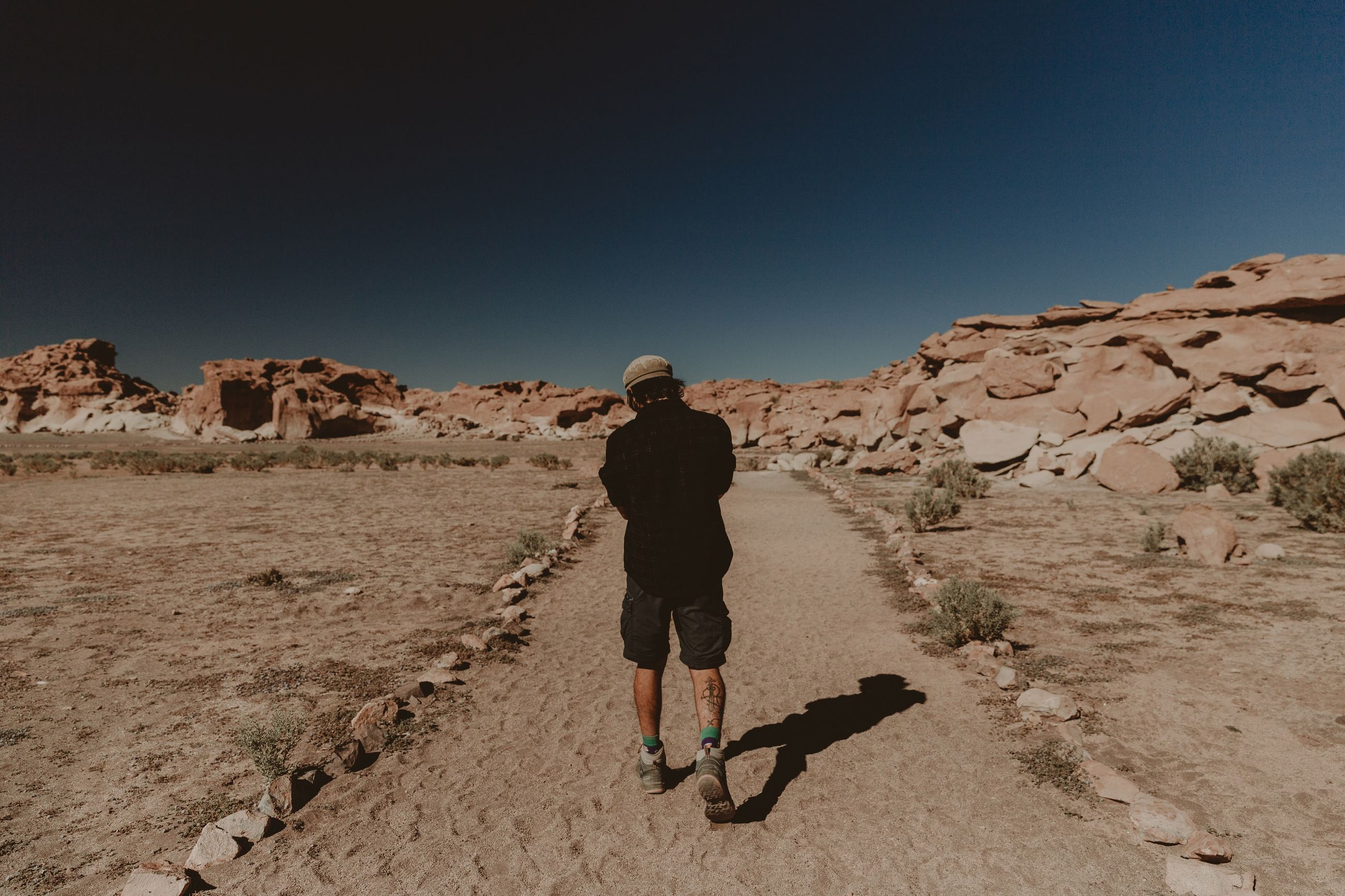 full length, real people, sky, leisure activity, one person, rear view, lifestyles, clear sky, nature, men, beauty in nature, copy space, sunlight, walking, scenics - nature, rock, non-urban scene, land, casual clothing, outdoors