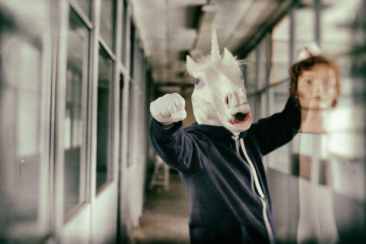 Man wearing horse mask standing in corridor
