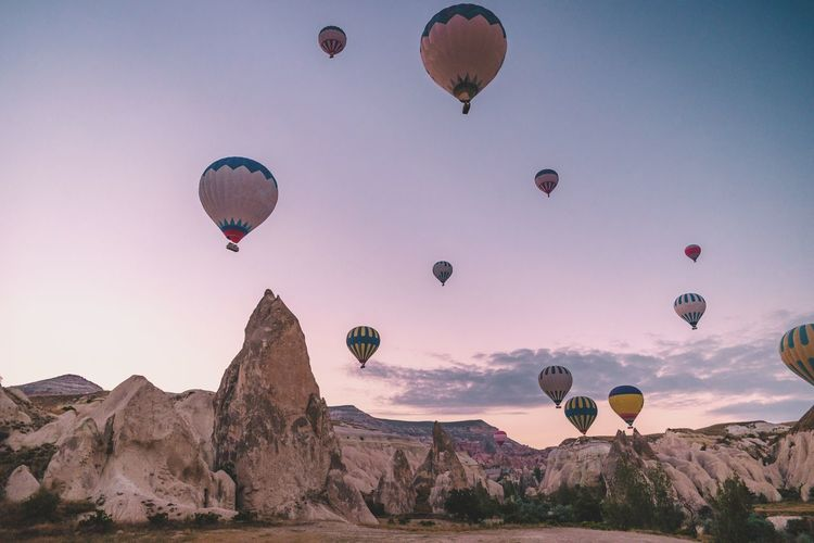 Low angle view of hot air balloons flying over landscape against sky during sunset
