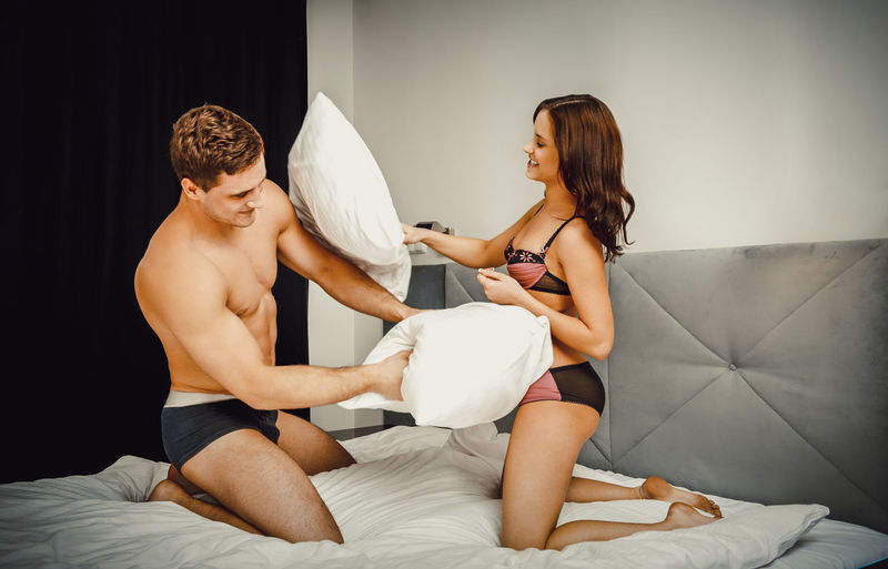 Young couple pillow fighting while kneeling on bed at home