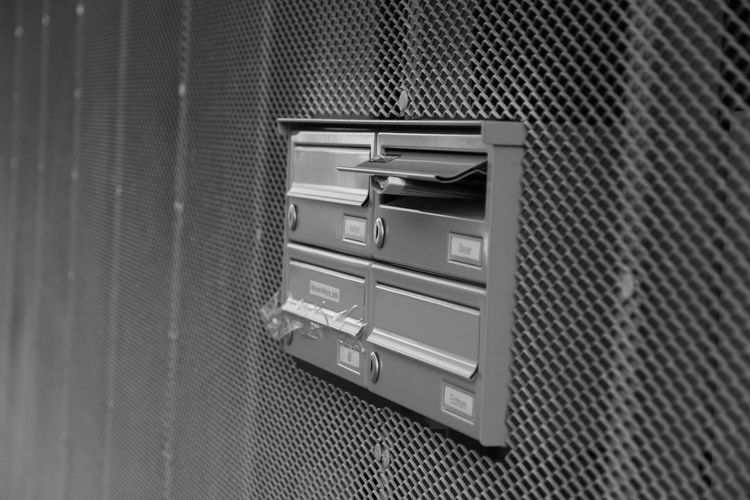 Mail in mailbox on metallic patterned wall at building