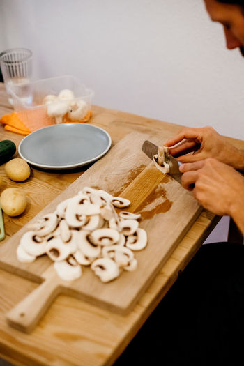 hands of a man cutting white mushrooms on a wooden cutting board as a topping for a pizza Indoors  Food And Drink Food Nutrition Ingredient Ingredients Italia Italian Food Pizza Pizza Time Human Hand Hand Freshness One Person Cutting Board Human Body Part Preparation  Table Kitchen Utensil Wood - Material Lifestyles High Angle View Preparing Food Mushroom Mushrooms Cutting Dish Working