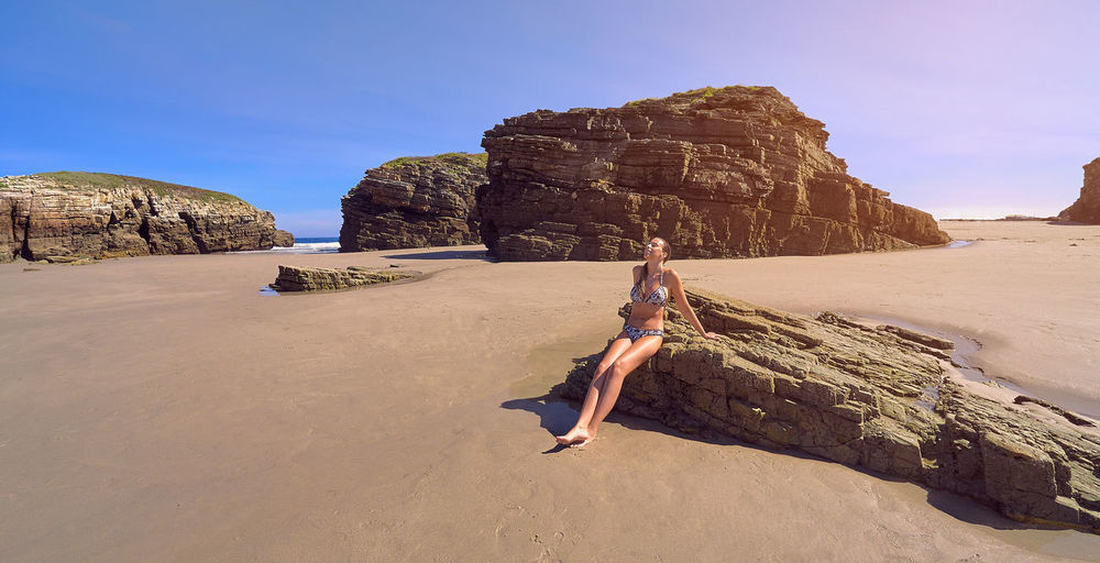 Full length of woman sitting on rock at beach against sky