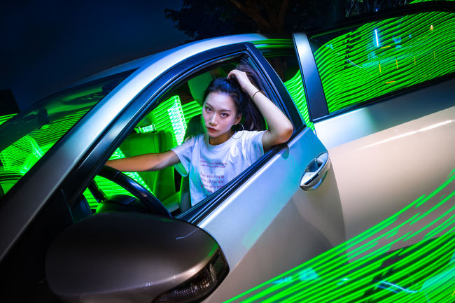 Light Painting Adult Car Casual Clothing Front View Happiness Leisure Activity Levin Lifestyles Light Painting Photography. Long Exposure Looking At Camera Mode Of Transportation Motor Vehicle Neon Lights Night One Person Outdoors Portrait Real People Sitting Smiling Toyota Transportation Women
