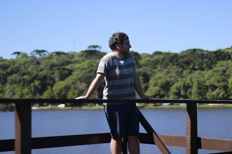 Young man looking at view while standing on footbridge against lake