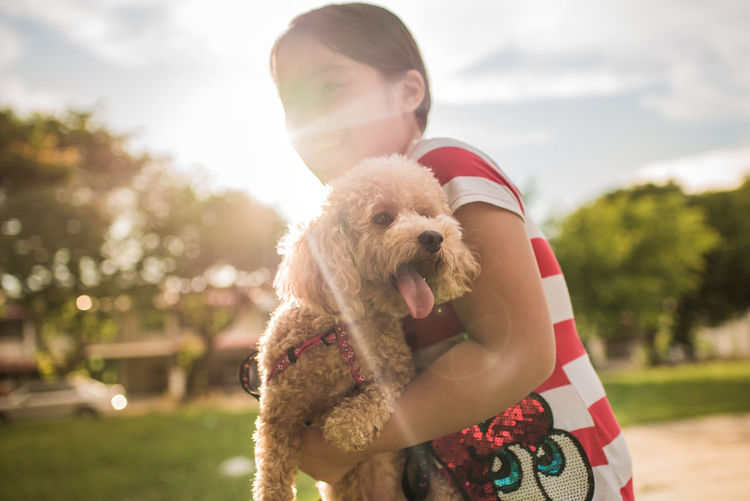 Smiling girl carrying poodle puppy while standing on field