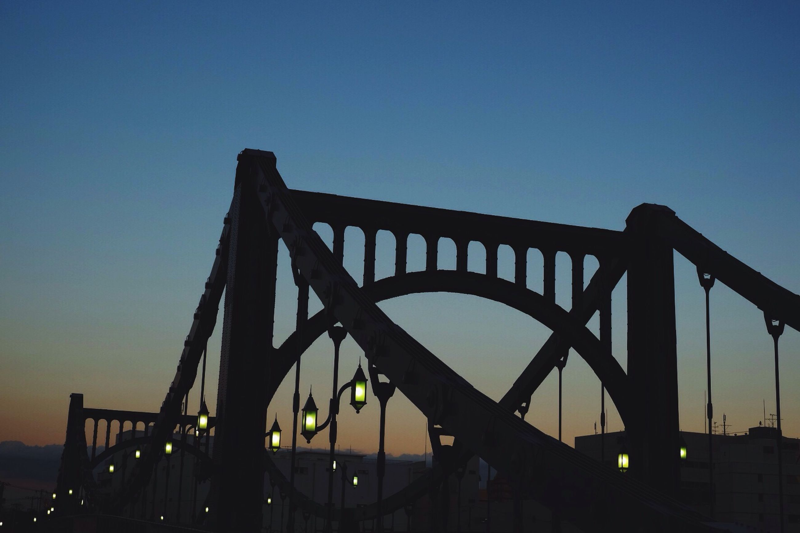 clear sky, silhouette, built structure, sunset, low angle view, architecture, connection, copy space, bridge - man made structure, engineering, sky, dusk, metal, bridge, blue, railing, outdoors, sunlight, no people, nature