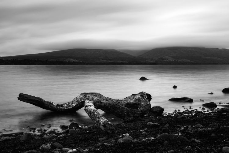 Long exposure overlooking Loch Lomond Beach Beauty In Nature Beauty In Nature Cloud - Sky Day Dead Wood Famous Place Highlands Iconic Lake Loch Lomond Long Exposure Mountain Mountain Range Nature No People Outdoors Rotten Scenic Scenics Scotland Sky Tranquil Scene Tranquility Water