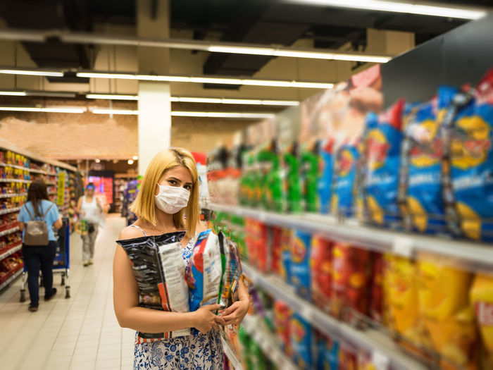 Portrait of young woman wearing mask holding chips standing at mall
