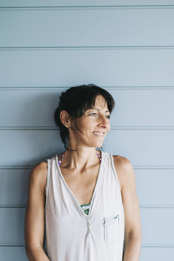 Smiling woman standing against wall