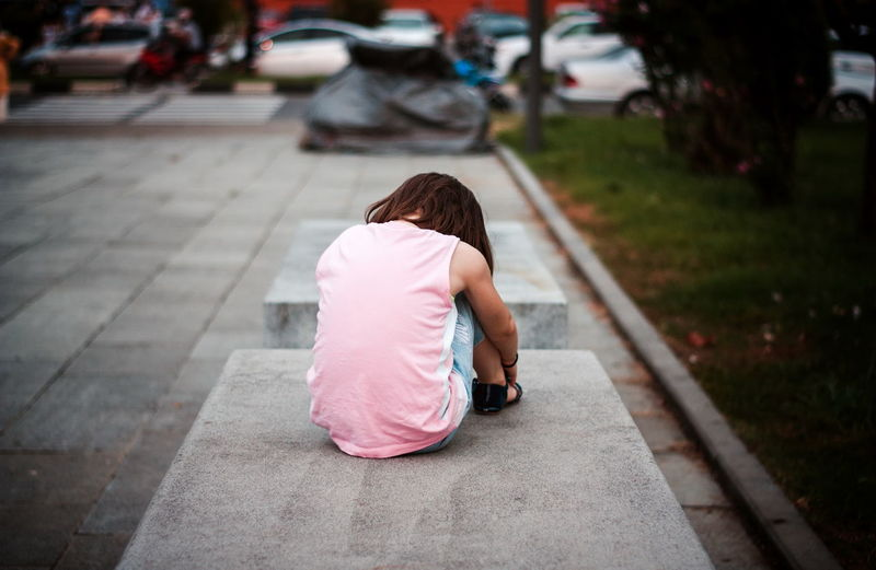 Little girl sitting alone on the bench