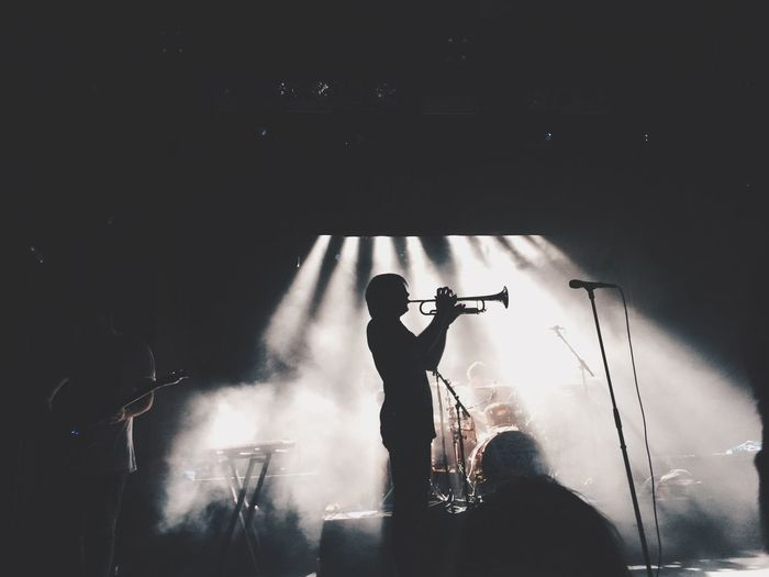 Silhouette man playing trumpet with performer in smoke