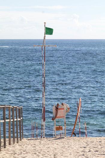 Flag by lifeguard chair at beach