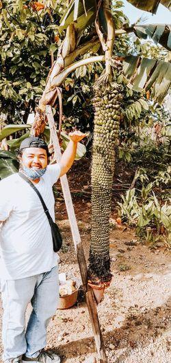 Full length portrait of man standing on tree
