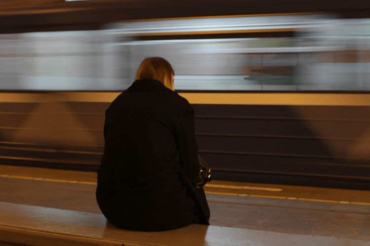 Rear view of woman sitting in front of train at railroad station platform