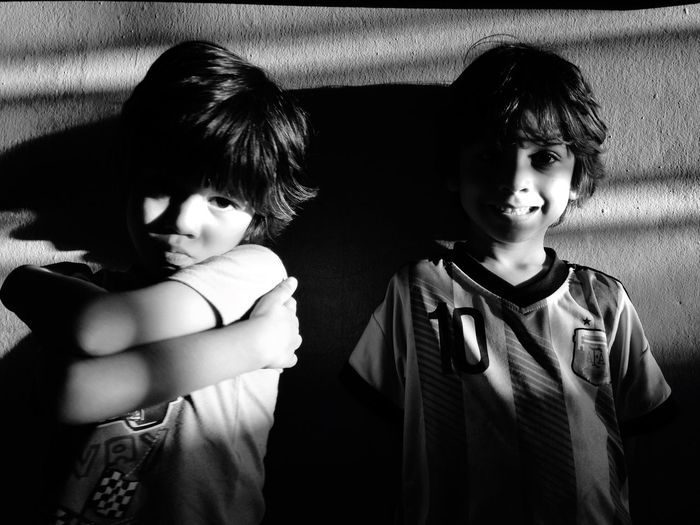 Portrait Of Two Boys Leaning Against Wall