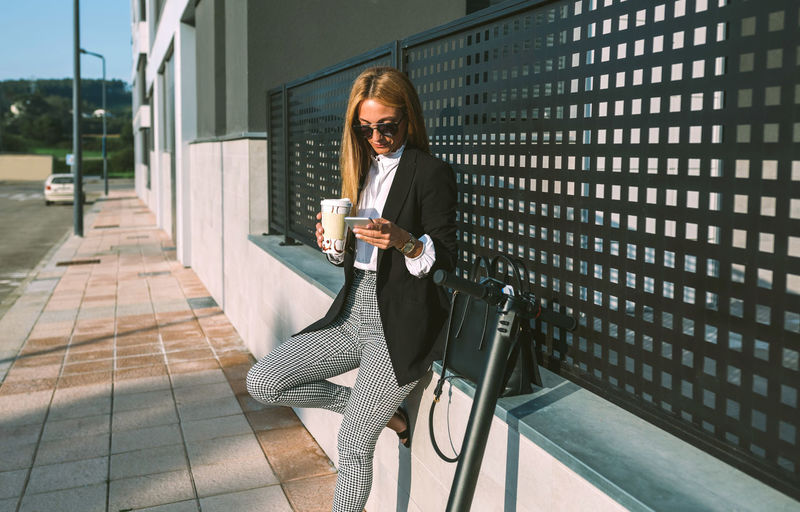 Full length of woman sitting on mobile phone
