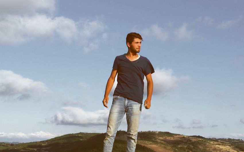 Young man standing on land against sky
