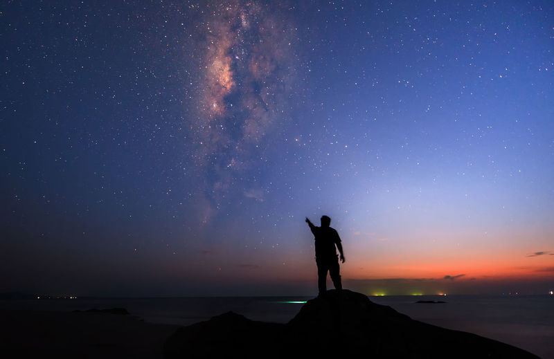 Silhouette man standing while pointing at galaxy in sky