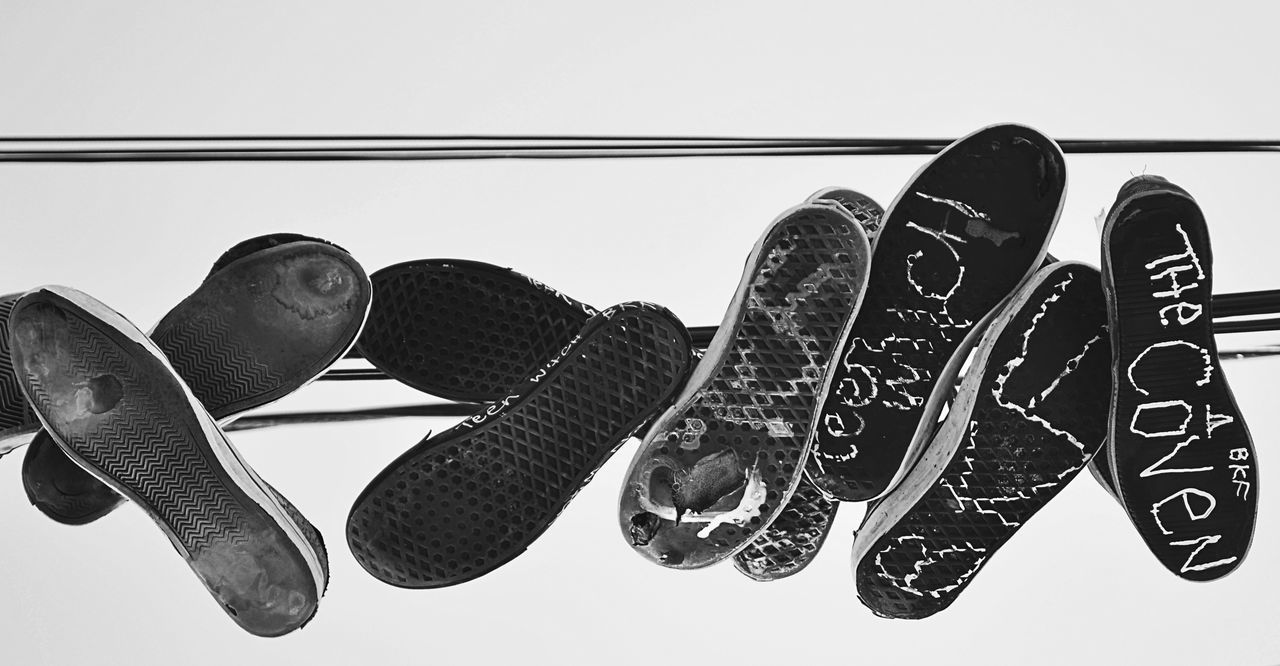 CLOSE-UP OF SHOES HANGING ON CLOTHESLINE