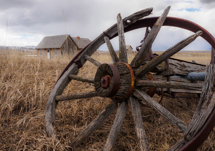 Close-Up Of Abandoned Wheel On Grassy Field Against Cloudy Sky