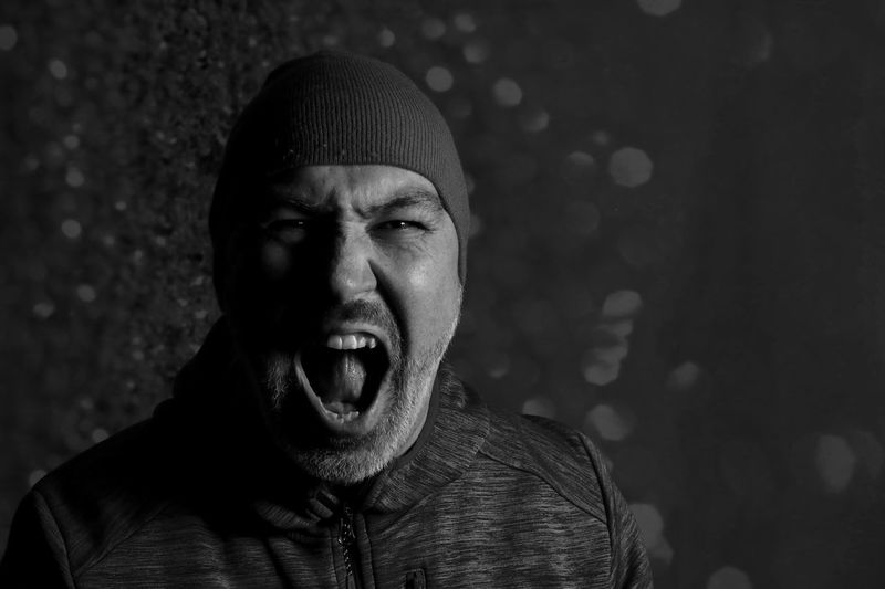 Close-up portrait of man screaming against wall